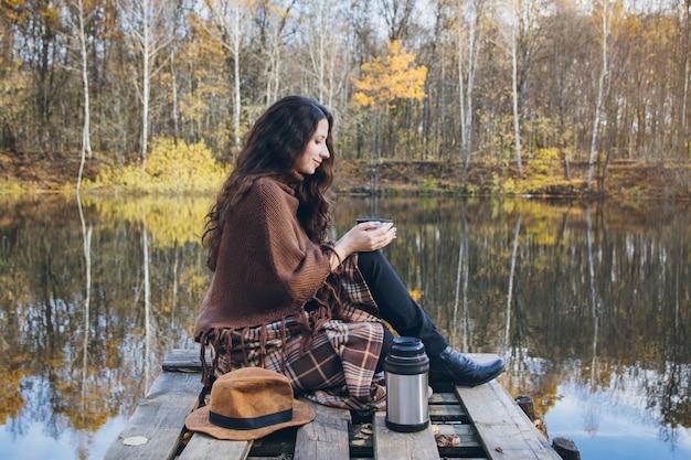 Meisje het drinken thee op een houten brug op een meer Premium Foto