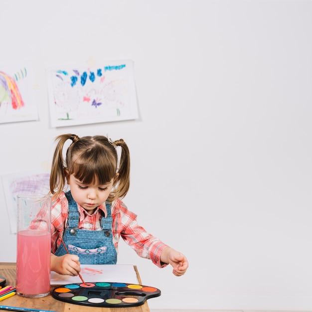 Meisje het schilderen met aquarelle bij houten lijst Gratis Foto