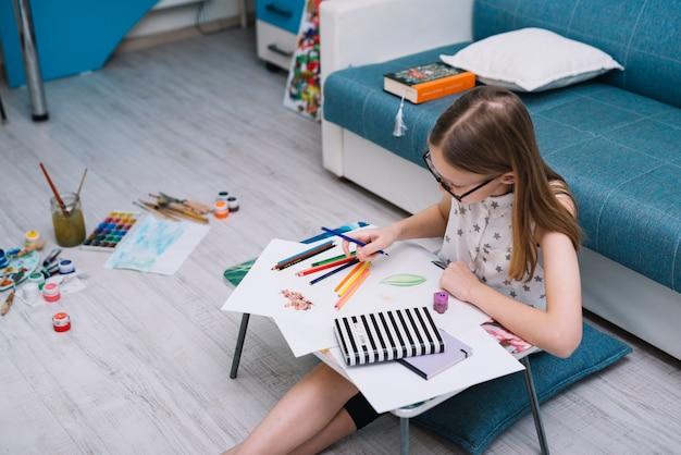 Meisje het schilderen op papier bij lijst met reeks potloden in ruimte met waterkleuren op vloer Gratis Foto