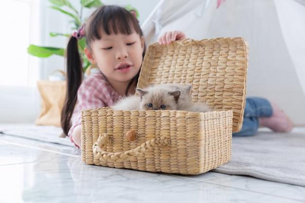 Meisje het spelen met kat in de houten mand thuis, vriendschapsconcept. Premium Foto