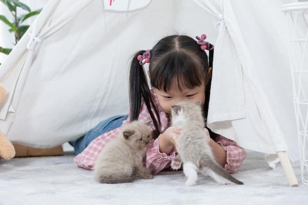 Meisje het spelen met kat thuis, het concept van het vriendenschip. Premium Foto