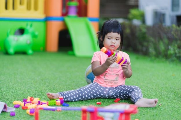 Meisje het spelen stuk speelgoed kleurrijke plastic blokken in speelplaats Premium Foto