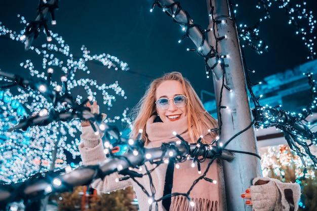 Meisje het stellen tegen de achtergrond van verfraaide bomen Gratis Foto