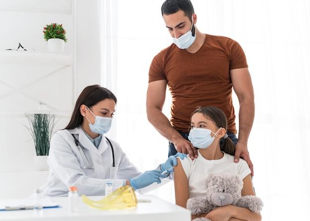 Meisje houdt haar speeltje vast terwijl ze wordt ingeënt Gratis Foto