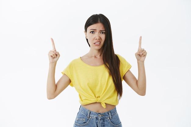 Meisje houdt niet van wat te zien. ontevreden, onhandig en niet onder de indruk goed uitziende vrouw in geel t-shirt handen omhoog Gratis Foto