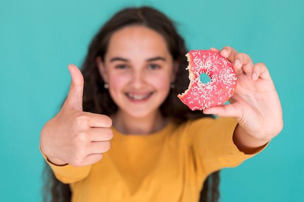 Meisje houdt van een geglazuurde donut Gratis Foto