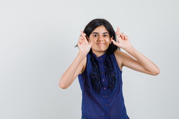 Meisje houdt vingers gekruist in blauwe blouse en kijkt hoopvol Gratis Foto