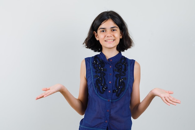 Meisje in blauwe blouse die iets beweert te laten zien en blij kijkt Gratis Foto