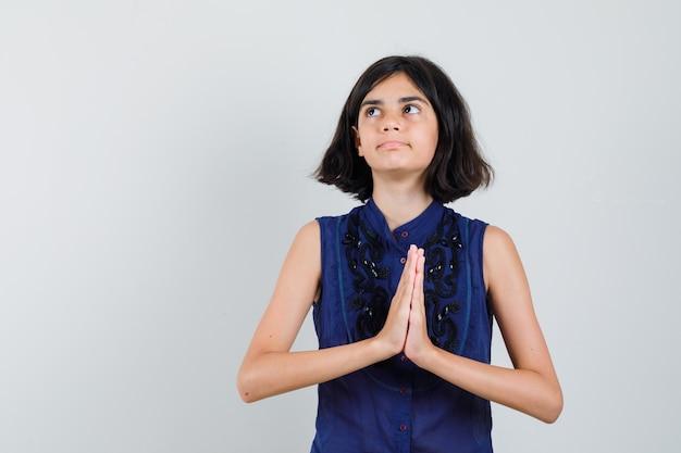 Meisje in blauwe blouse die namaste-gebaar toont en peinzend kijkt Gratis Foto