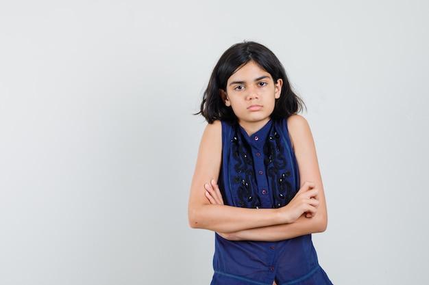 Meisje in blauwe blouse die zich met gekruiste armen bevindt en boos kijkt Gratis Foto
