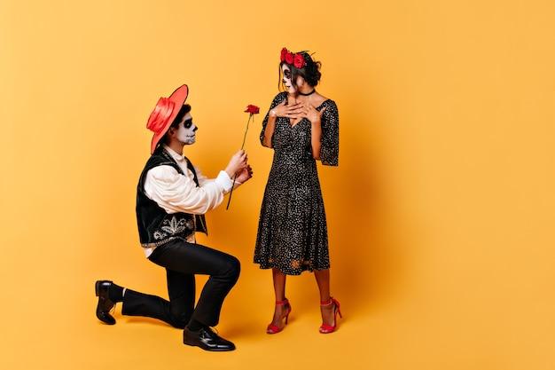 Meisje in bolletjesjurk met bloemen in het haar is aangenaam verrast door de daad van haar jonge man. man in sombrero geeft rode roos aan zijn vrouw. Gratis Foto