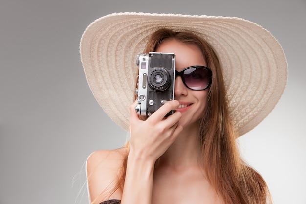 Meisje in breedgerande hoed en zonnebril met retro camera Gratis Foto
