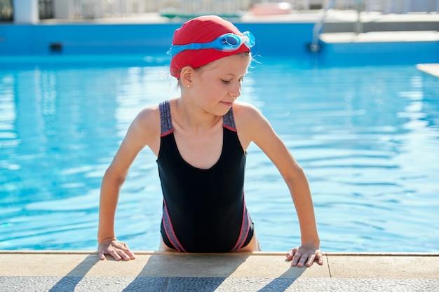 Meisje in buitenzwembad in badmuts, zwembroek en bril Premium Foto
