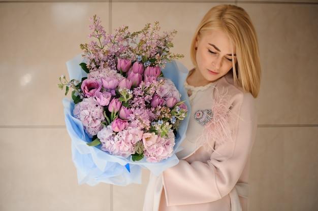 Meisje in de jas met een boeket van paarse violet tulpen en lila Premium Foto