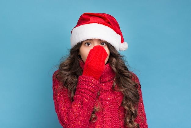 Meisje in de winterkleren die haar gezicht behandelen met haar hand Gratis Foto