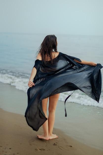 Meisje in een badpak en een zwarte cape dansen op het zand, de zee, het strand, het achteraanzicht Premium Foto
