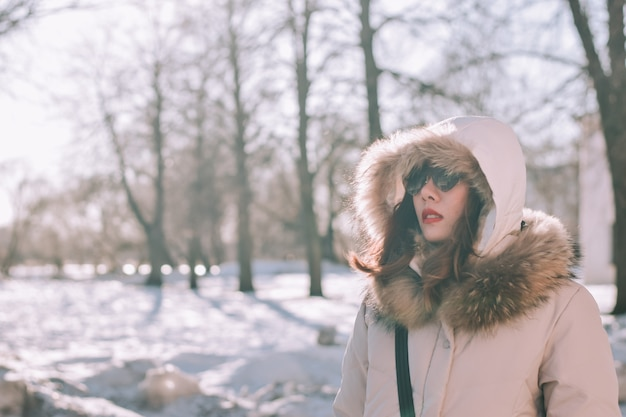 Meisje in een de winterpark in de middag in sneeuwval Premium Foto