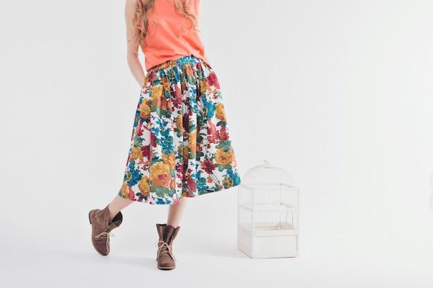 Meisje in een gekleurde rok en schoenen op wit Premium Foto