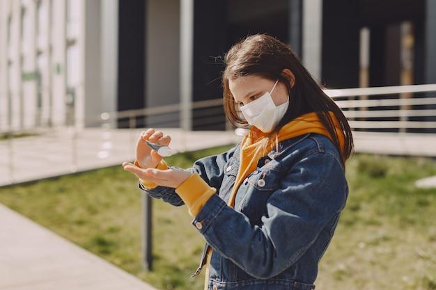 Meisje in een masker staat op straat Gratis Foto