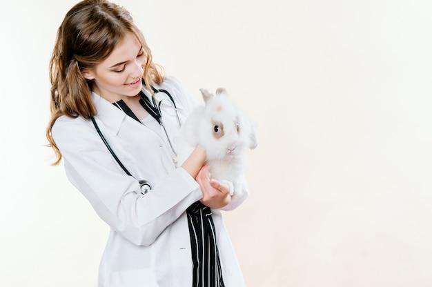 Meisje in een pak van een arts een dierenarts met een konijn in haar handen Premium Foto