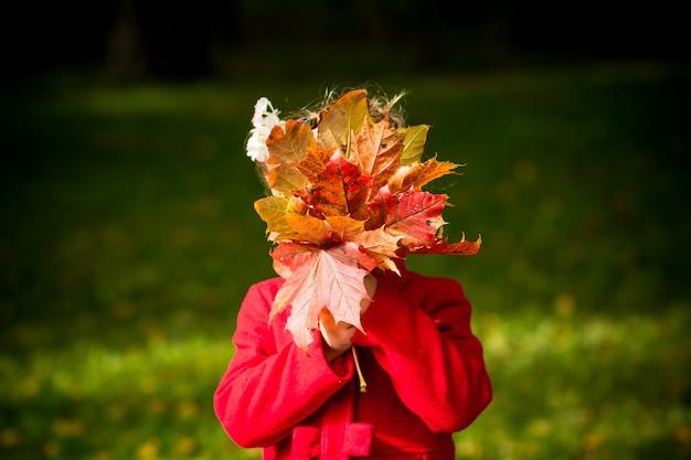 Meisje in een rode jas met herfstbladeren in het schoonheidspark Premium Foto