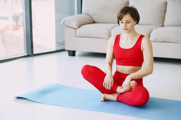 Meisje in een rode sport uniforme beoefenen van yoga thuis Gratis Foto