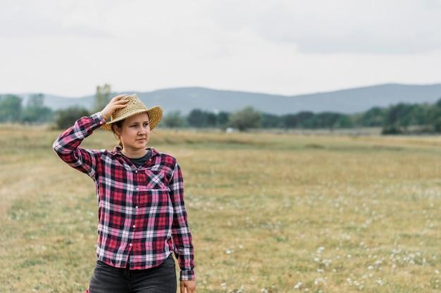 Meisje in een rode vierkante shit die haar hoed op het gebied houdt Gratis Foto