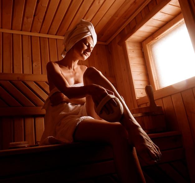 Meisje in een spa-behandeling in een traditionele sauna met een borstel voor de huid en een washandje. Premium Foto