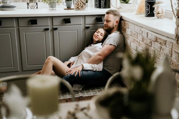 Meisje in een wit overhemd en een kerel in een grijze t-shirt in de keuken. kus en knuffel. Premium Foto