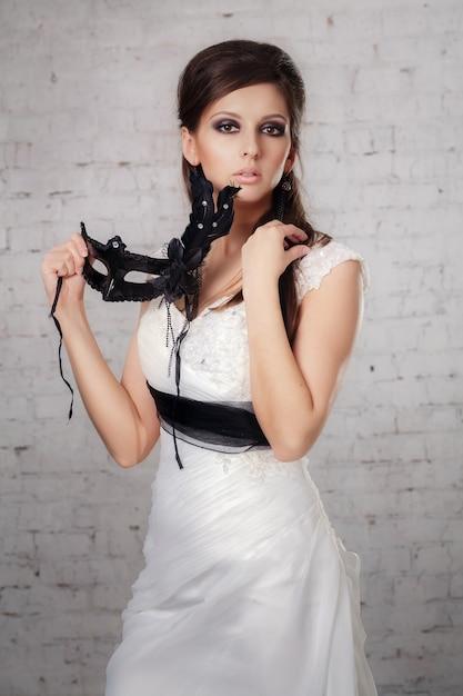 Meisje in een witte jurk met een zwart masker in de studio Premium Foto