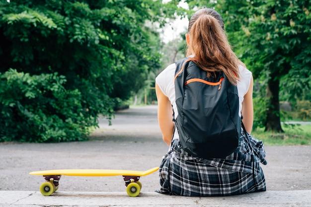 Meisje in jeans, t-shirt en sneakers, die op de stappen naast haar gele skateboard zit Premium Foto