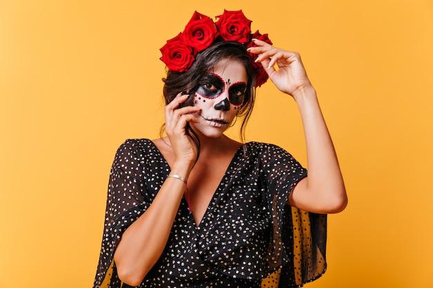 Meisje in jurk met v-hals en wijde mouwen poseert voor portret op geïsoleerde muur. mexicaans meisje met rozen op haar hoofd Gratis Foto