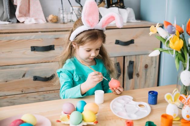 Meisje in konijntjesoren die eieren voor pasen schilderen Gratis Foto