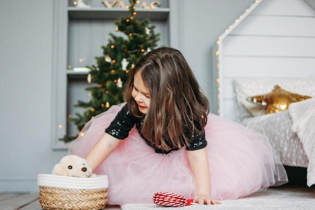 Meisje in mooie kleding met hondstuk speelgoed in de ruimte van de bedruimte van kerstboom Premium Foto
