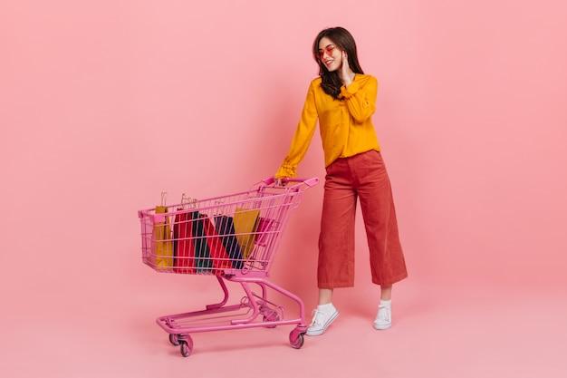 Meisje in oranje blouse en zonnebril met glimlach kijkt naar veel van haar aankopen liggend in roze trolley van supermarkt. Gratis Foto