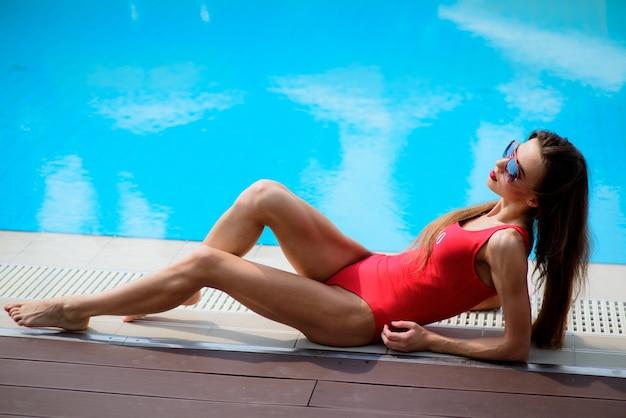 Meisje in rood zwempak ligt bij het blauwe zwembad Gratis Foto
