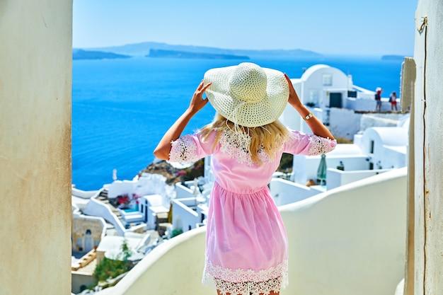Meisje in roze met een strooien hoed, uitzicht vanaf de achterkant in oia, santorini, griekenland eiland. meisjestoerist in europees Premium Foto