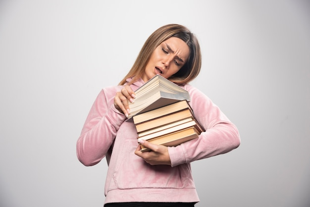Meisje in roze swaetshirt dat een voorraad boeken vasthoudt, een bovenaan opent en het leest Gratis Foto