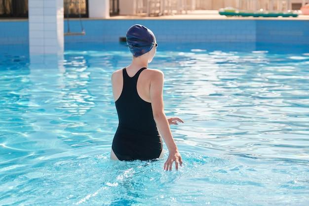 Meisje in sport zwembroek en badmuts invoeren van het buitenzwembad. Premium Foto