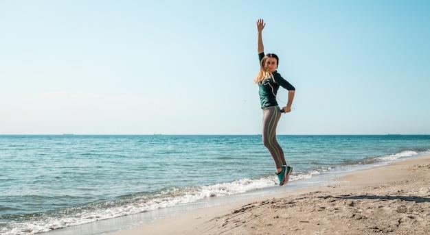 Meisje in sportkleding fitness door de zee te luisteren Gratis Foto