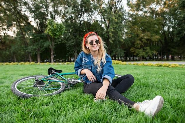 Meisje in stijlvolle kleding, zittend op het groene gazon in een park met een fiets en ontspannen. Premium Foto
