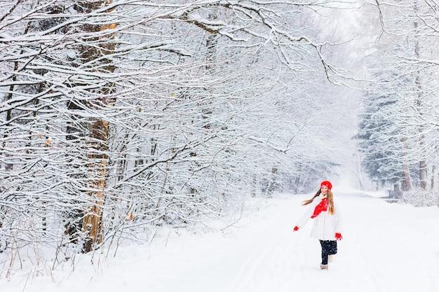 Meisje in warme kleren rennen en glimlachen in een winterpark tussen de sneeuw Premium Foto