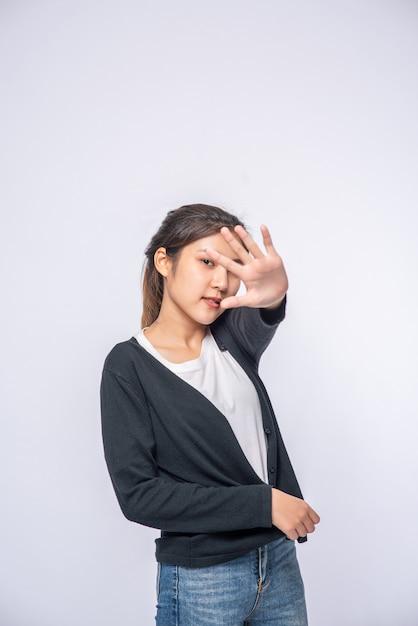 Meisje in witte rekjeans en handverbodsteken op witte muur. Gratis Foto