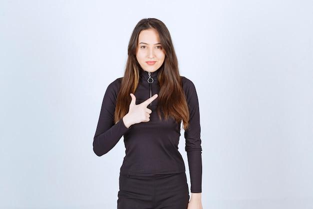 Meisje in zwarte kleding die op iets wijst. Gratis Foto
