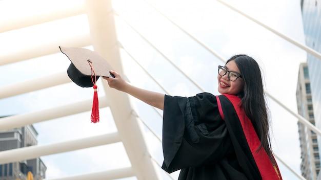 Meisje in zwarte toga's en houd diploma certificaat lachend met gelukkig afgestudeerd. Premium Foto