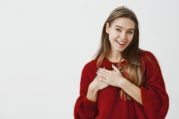 Meisje is blij met complimenten van corowker op kantoor. aangeraakt charmant europees vrouwelijk model in stijlvolle rode losse trui, met palm op de borst en glimlachend van tevredenheid over grijze muur Gratis Foto