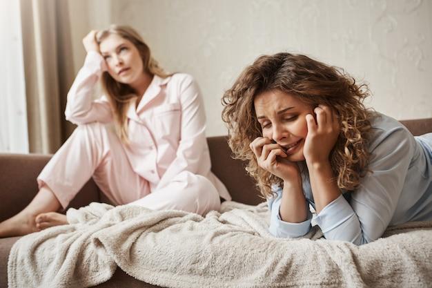Meisje kan niet omgaan met druk, ze voelt zich ellendig en verdrietig. sombere huilende vrouw die in nachtkleding op de bank ligt, zeurt en klaagt over het leven terwijl vriendin zich stoort aan een stom gesprek Gratis Foto