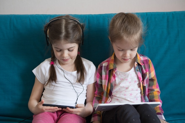 Meisje kijken naar tekenfilms op een tablet en spelletjes spelen Premium Foto