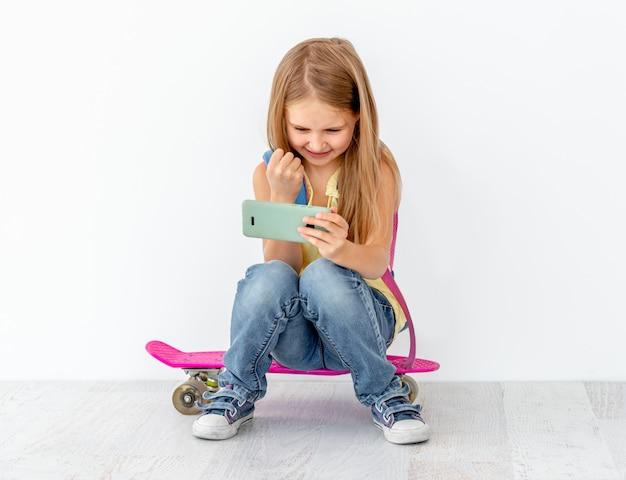 Meisje kijken telefoon, zittend op skate Premium Foto