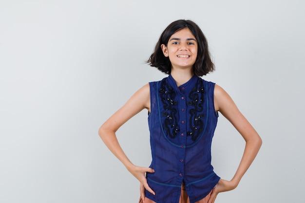 Meisje kijkt naar voorkant in blauwe blouse, rok en kijkt vrolijk. Gratis Foto